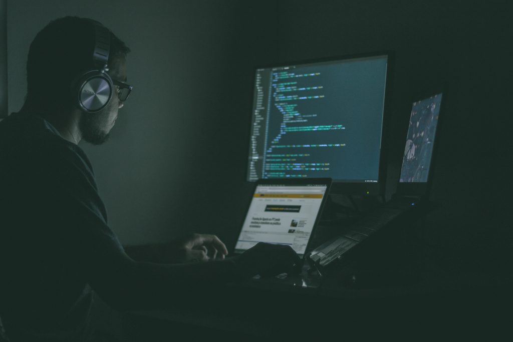 A man sits in a shadowy room in front of multiple computer screens. One is running a coding language.